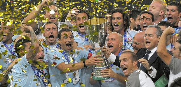 Players of Lazio celebrate with the winning trophy on the podium after defeating Inter Milan during the Italian Super Cup match at the National Stadium, also known as the Bird's Nest in Beijing on August 8, 2009. Lazio defeated Inter Milan 2-1. AFP PHOTO/LIU Jin